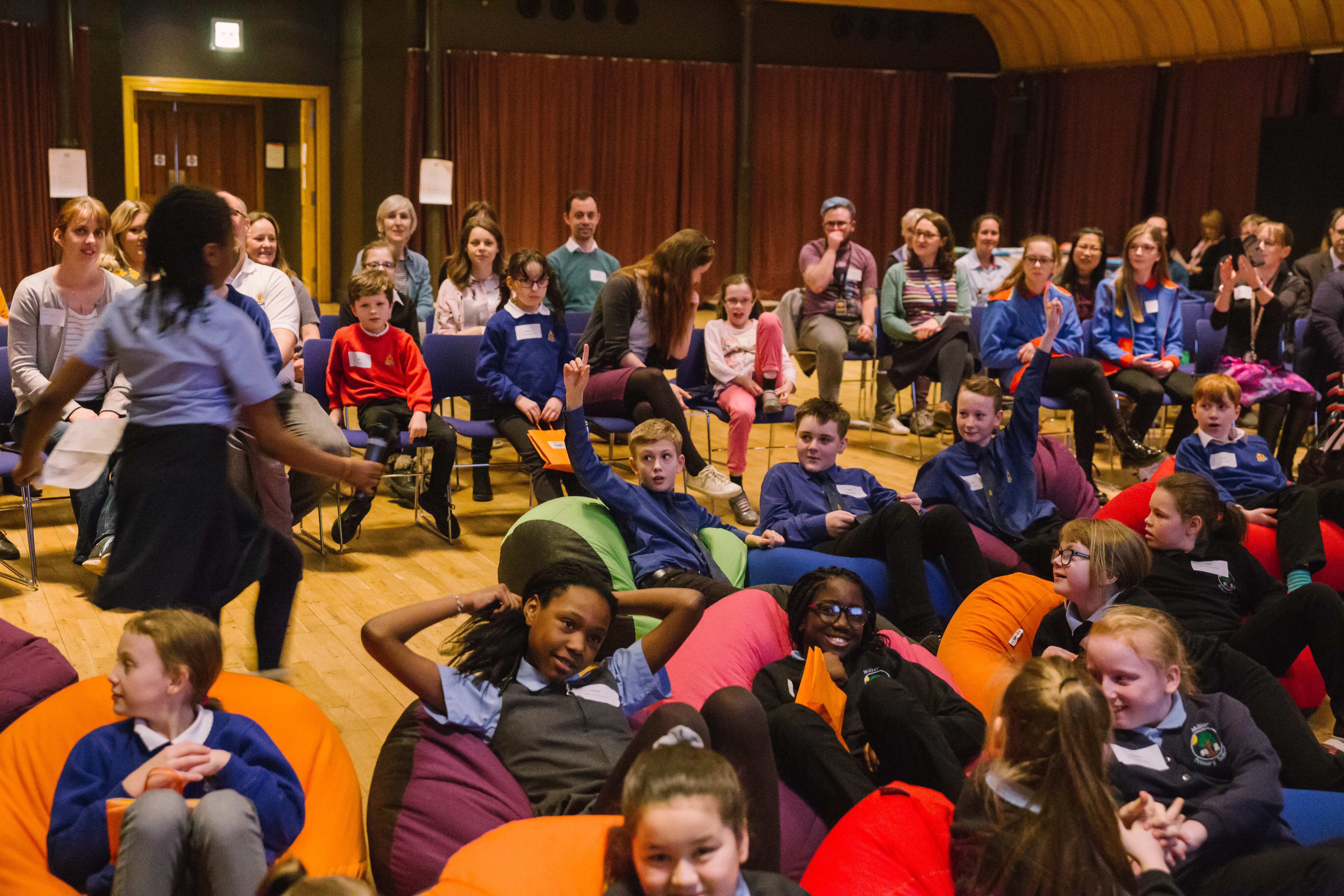 Young people sit in a hall, some on beanbags some on chairs
