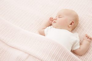 A baby sleeps on its back, arms raised. It is tucked under a pink blanket
